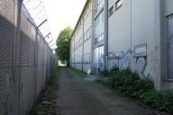 Berlin Cité Pasteur: ehem. französisches Gymnasium am Schutzzaun des Flughafen Tegel